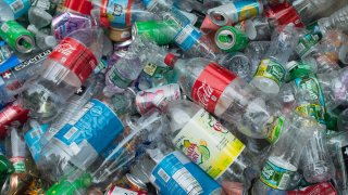 A large pile of plastic bottles and cans collected on a street corner in downtown Manhattan, New York.