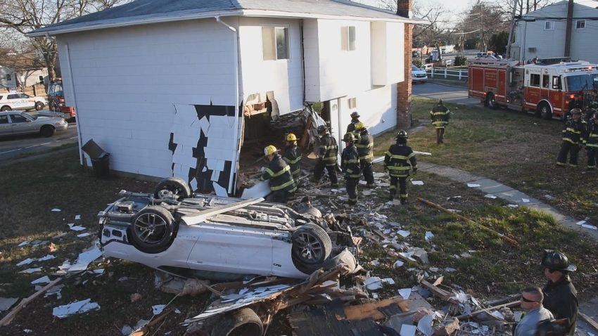 car lies upside down next to house