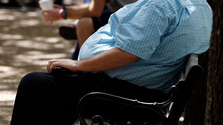 In this Thursday, Sept. 4, 2014, file photo, an overweight man rests on a bench in Jackson, Miss.