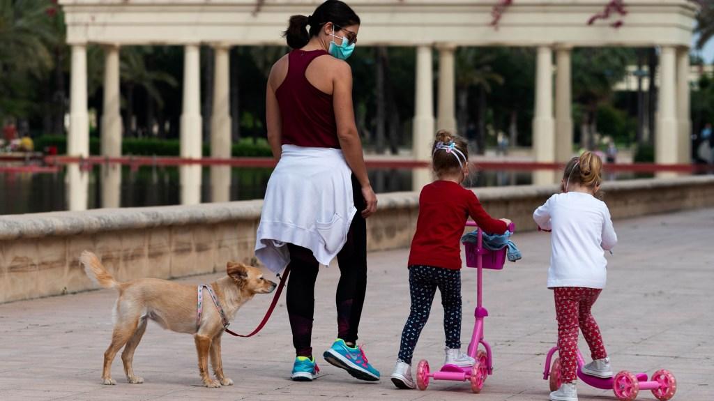 Dos niñas salen a la calle luego de varias semanas de cuarentena en España.