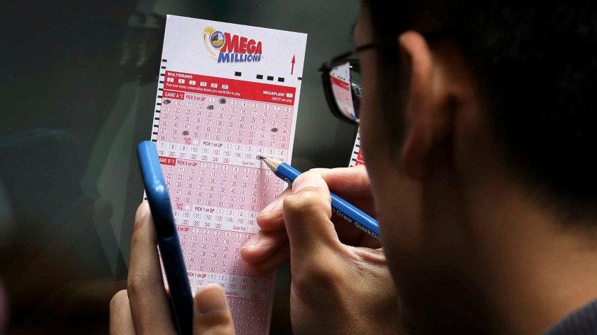 Customers fill out Mega Millions lottery tickets outside of a convenience store in Lower Manhattan, October 23, 2018 in New York City.