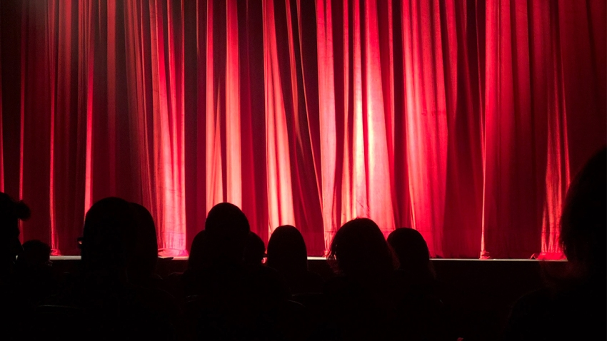 View of a theater stage with the curtains closed