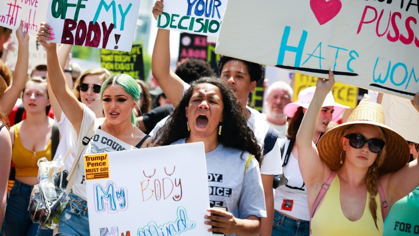 """Demonstrators hold signs during a protest against Georgia's """"heartbeat"""" abortion bill outside of the Georgia State Capitol building in Atlanta, Georgia, U.S., on Saturday, May 25, 2019. People gathered to protest the state's recently passed House Bill 481, which would banabortionafter a doctor can detect a fetal heartbeat usually around the sixth week of pregnancy."""