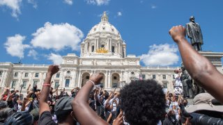Supporters raise their fists while standing at the Minnesota State Capitol.