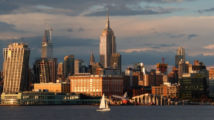 A boat sails in the Hudson River under the Empire State Building and Chrysler Building