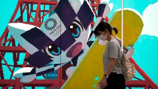 A pedestrian wearing a protective mask walks past an advertisement for the now-postponed Tokyo 2020 Olympic and Paralympic Games in Tokyo, Japan, June 8, 2020.