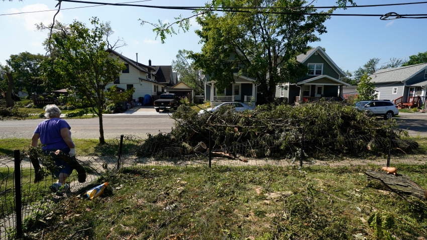 A woman hauls branches from a neighbor's yard to the street, Friday, Aug. 14, 2020, in Cedar Rapids, Iowa.