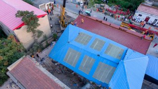 rescue workers are seen near the site of a collapsed two-story restaurant in Xiangfen County of Linfen City, northern China's Shanxi Province, Saturday, Aug. 29, 2020