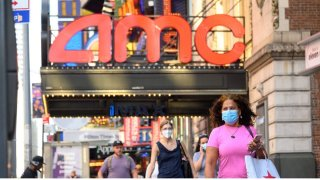 People pass by the closed AMC Theater in midtown Manhattan.