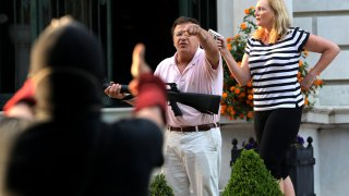 In this June 28, 2020, file photo, armed homeowners Mark T. and Patricia N. McCloskey stand in front their house along Portland Place as they confront protesters marching to St. Louis Mayor Lyda Krewson's house in the Central West End of St. Louis.