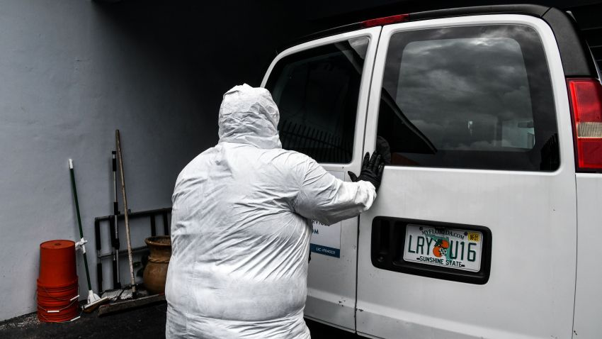 "Funeral assistant, Bradley Georges 26 pull out a stretcher from a van wearing a PPE kit prior to a funeral at one of Miami's largest funeral homes, Van Orsdel funeral homes in Miami, on July 17, 2020. - For one young funeral assistant in Florida, his social life has been dead -- his only human interactions are coronavirus victims at the funeral home where he works. But he doesn't regret his isolation. The pandemic is ""bigger than we are,"" said Bradley Georges, 26, an assistant at the Van Orsdel funeral home in Miami."