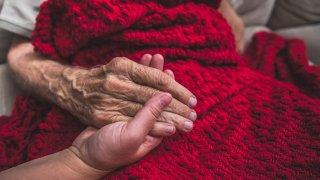 Caretaker holding elderly patient's hand