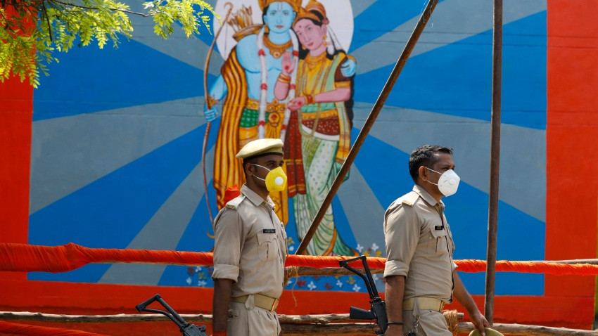 Policemen walk past an image of Hindu god Ram on the eve of a groundbreaking ceremony of a temple dedicated to Ram in Ayodhya, India, Tuesday, Aug. 4, 2020.