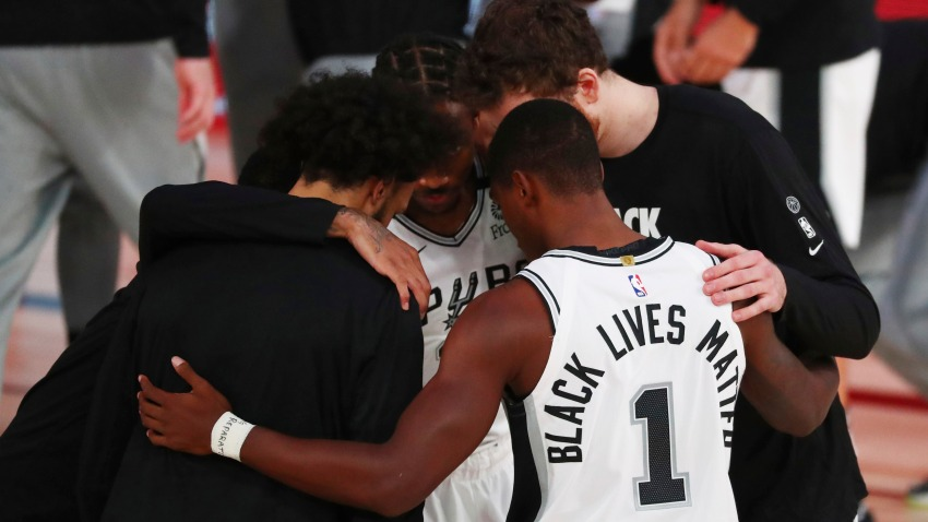 In this July 31, 2020, file photo, San Antonio Spurs guard Lonnie Walker IV (1) has Black Lives Matters on the back of his jersey in a huddle before an NBA basketball game against the Sacramento Kings in Lake Buena Vista, Fla.