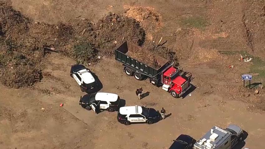 Police officers investigate scene of fatal dump truck incident