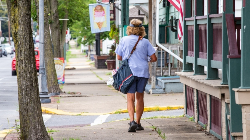 United States Postal Service letter carrier walks her route