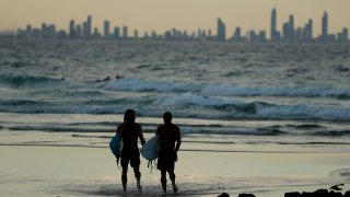 In this March 25, 2020, file photo, people are seen on the beach at Snapper Rocks, which is on the Queensland and New South Wales border at Coolangatta, in Gold Coast, Australia.