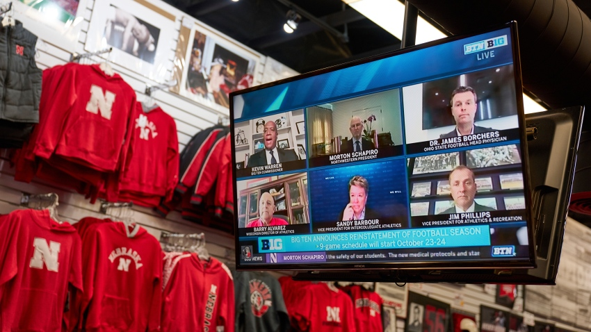 The Husker Hounds sports apparel store in Omaha, Neb., shows on television screens Wednesday, Sept. 16, 2020, a Big Ten virtual news conference to discuss the reopening of the football season. President Donald Trump was quick to spike the ball in celebration when the Big Ten announced the return of fall football at colleges clustered in some of the Midwest battleground states critical to his reelection effort.