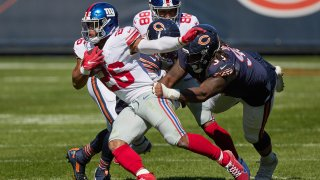 New York Giants running back Saquon Barkley (26) battles with Chicago Bears defensive tackle John Jenkins (90)