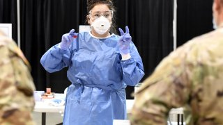 Respiratory therapist Diana Vega from University Medical Center of Southern Nevada goes over testing procedures with members of the Nevada National Guard during a preview of a new coronavirus (COVID-19) testing site inside Cashman Center on August 3, 2020 in Las Vegas, Nevada.