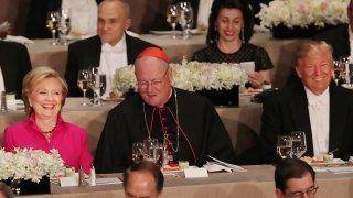 ardinal Timothy Dolan sits between, Hillary Clinton and Donald Trump