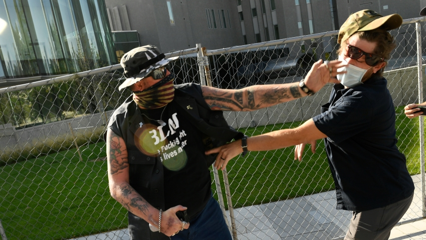 In this Oct. 10, 2020, file photo, a man punches another man after a rally in Denver, Colorado.