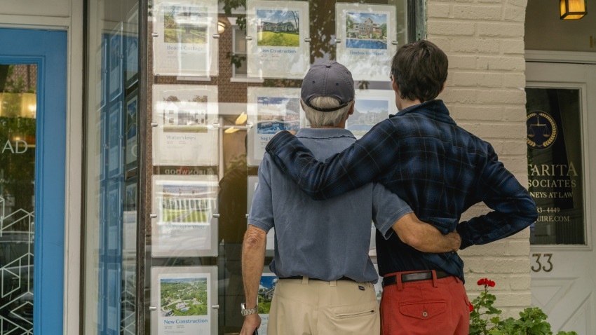 Pedestrians view homes for sale displayed in the window of a real estate office in Southampton, New York