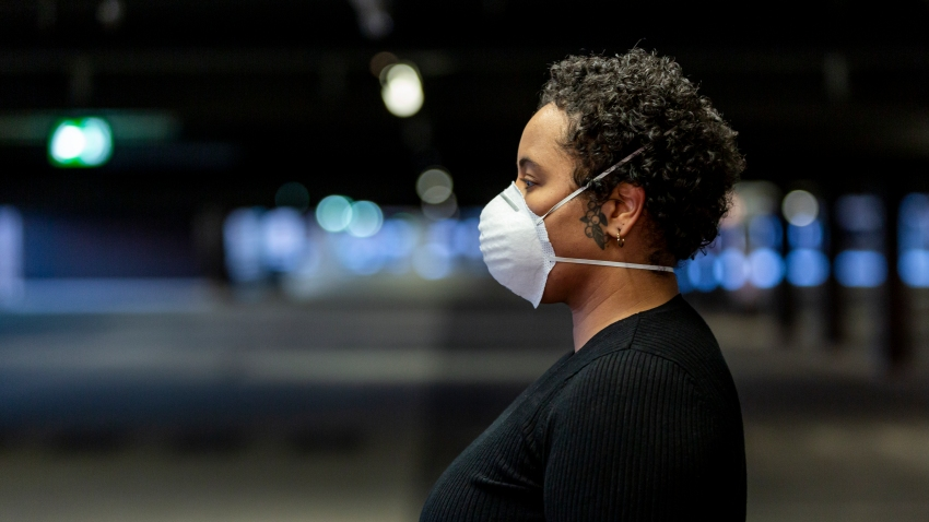 Young woman wearing a protective face mask to prevent the spread of virus in the city