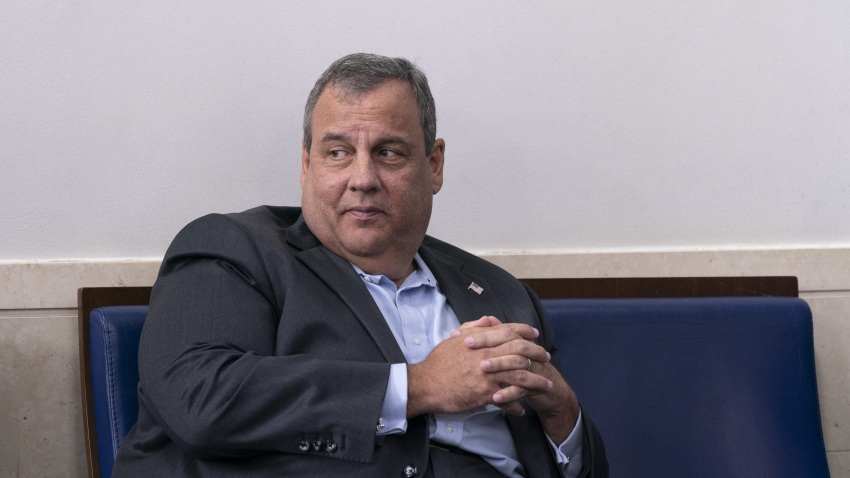 Former New Jersey Governor Chris Christie sits at the White House press room