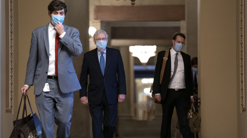 Senate Majority Leader Mitch McConnell, a Republican from Kentucky, center, wears a protective mask as he departs the U.S. Capitol