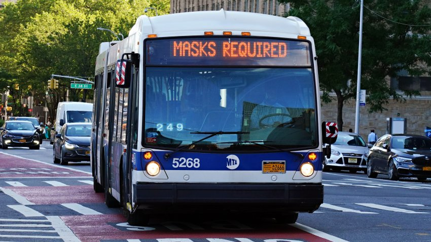 An MTA bus displays a 'MASKS REQUIRED' sign in New York City