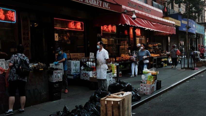 People walk past street vendors in New York City's Chinatown on August 10, 2020 in New York City.