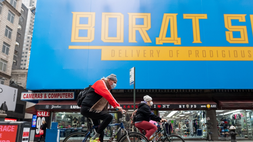 People ride bicycles by a billboard for Borat Subsequent Moviefilm in Times Square as the city continues the re-opening efforts following restrictions imposed to slow the spread of coronavirus on October 28, 2020 in New York City.