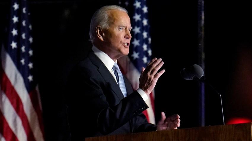 Joe Biden speaks with American flags in background