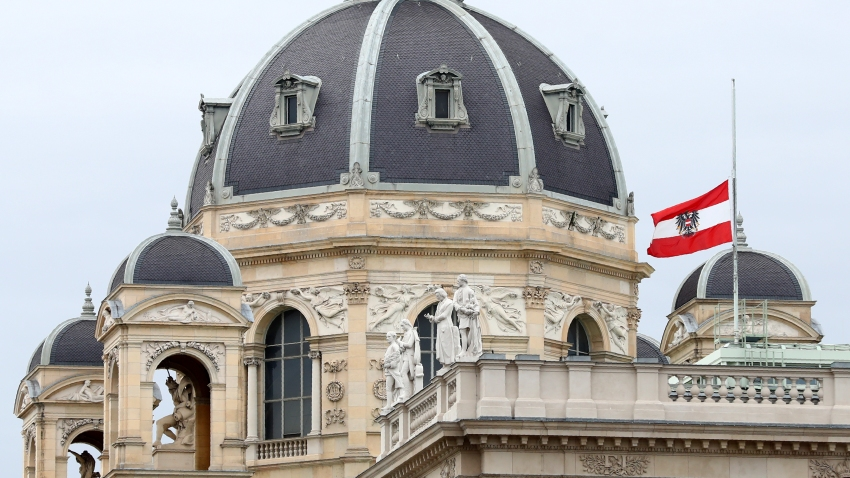 The Austrian national flag waves of half-mast on a building downtown in Vienna, Austria, Wednesday, Nov. 4, 2020. Several shots were fired shortly after 8 p.m. local time on Monday, Nov. 2, in a lively street in the city center of Vienna.