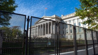 In this Nov. 3, 2020, file photo, the building of the U.S. Treasury Department can be seen behind the fence that provides extensive security for the White House on the day of the presidential election.