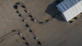 People in vehicles wait in line to enter a drive-thru COVID-19 testing site