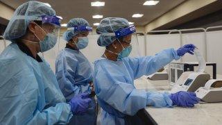 Healthcare workers prepare COVID test machine
