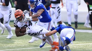 Vonn Bell #24 of the Cincinnati Bengals is tackled by Evan Engram #88 of the New York Giants