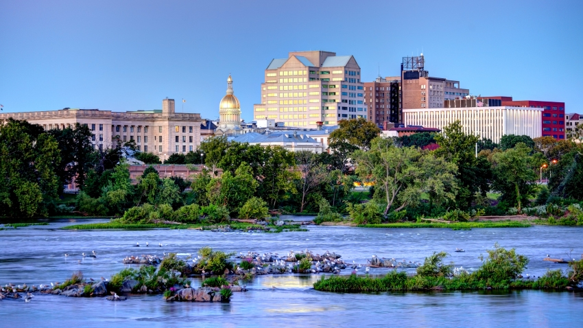 The skyline of Trenton, New Jersey, is shown behind a river.