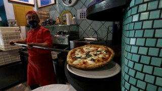 Eugenio Iorio wears a face mask to curb the spread of COVID-19 as he bakes a pizza at a restaurant in Naples, Italy