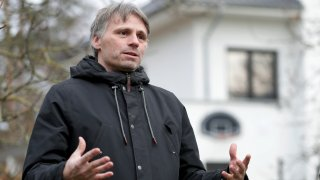 Fabian Leendertz speaks during an interview, with building in the background