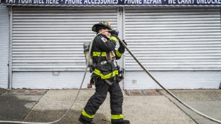 A firefighter is fixing a fire hose during the fire scene