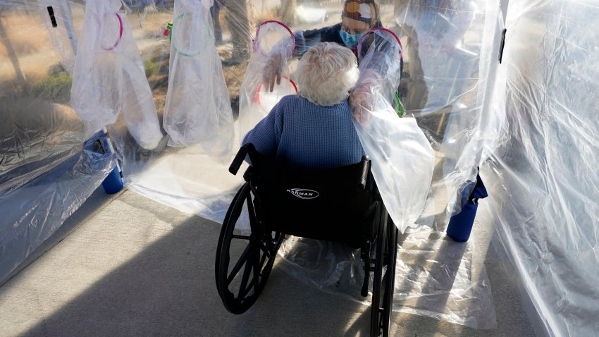 """Lara Angevine (R) reaches to hug her mother Barbara through the wall of a plastic """"hug tent"""" outside the Accel at Longmont skilled nursing facility on December 4, 2020 in Longmont, Colorado. The hug tent, built by TRU Community Care, allowed people from the outside to physically touch residents at the facility for the first time since the COVID-19 pandemic hit."""