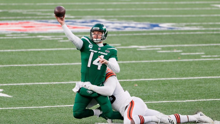 Sam Darnold #14 of the New York Jets throws away the ball as he is tackled by Myles Garrett #95 of the Cleveland Browns in the fourth quarter