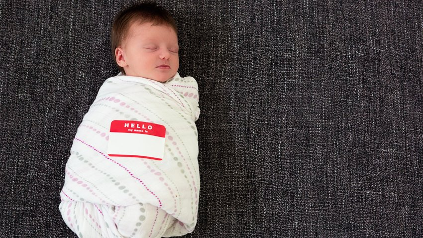 "Sleeping swaddled infant with a ""Hello my name is"" sticker."