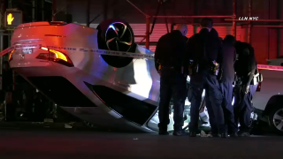 A white sedan rests upside down on an East Harlem street after its driver lost control and flipped the vehicle