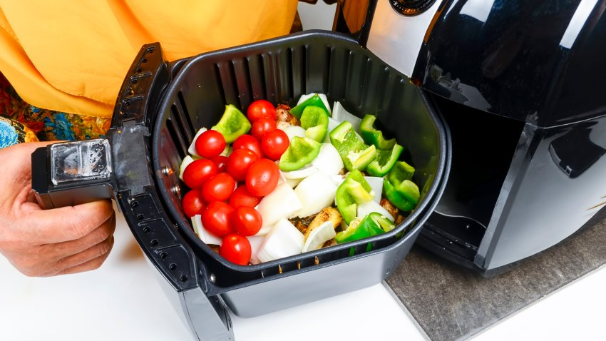 Seasoned vegetables are cooked in an air fryer.