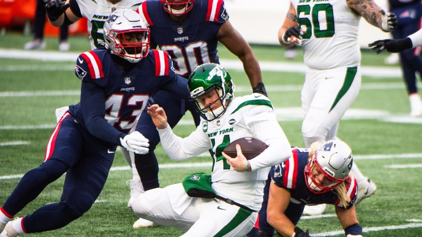Sam Darnold #14 of the New York Jets is tackled by Rashod Berry #43 of the New England Patriots