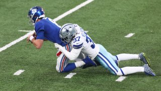 Daniel Jones #8 of the New York Giants is sacked by Donovan Wilson #37 of the Dallas Cowboys